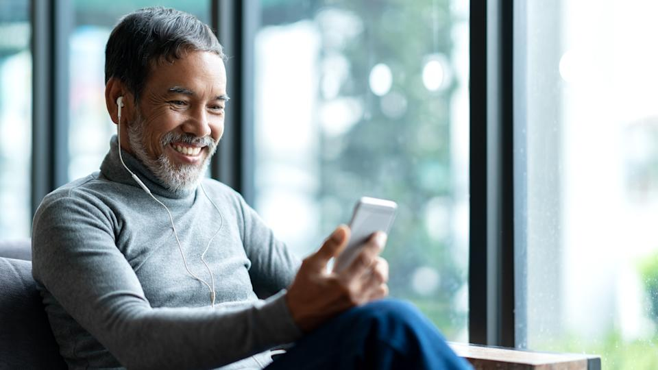 Portrait of attractive mature asian man retired with stylish short beard using smartphone sitting or listening music in urban lifestyle coffee shop.