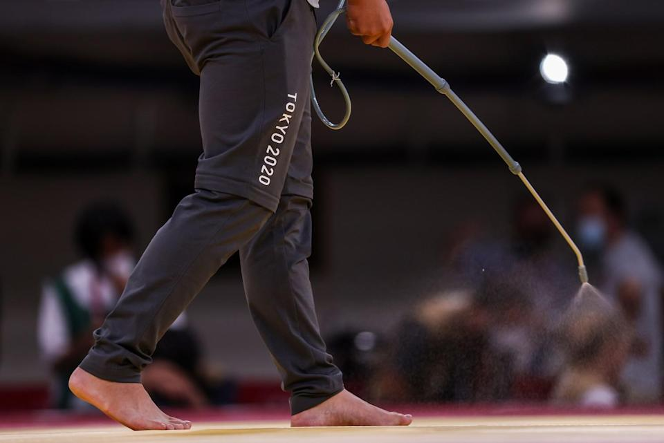 A worker sprays disinfectant between matches at the judo finals