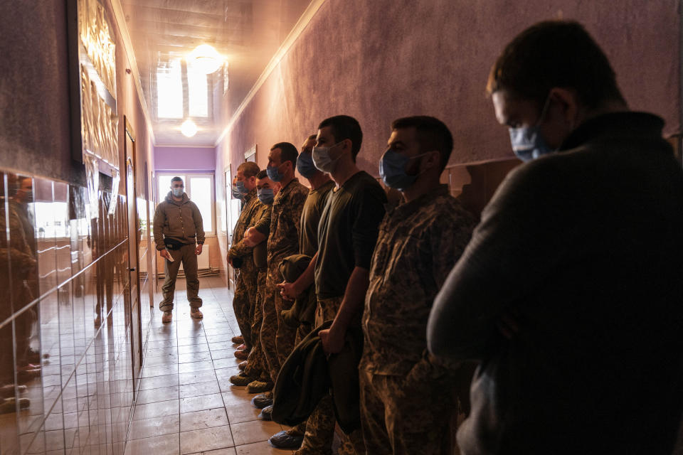 Ukrainian servicemen stand in line as they wait to receive a dose of the AstraZeneca COVID-19 vaccine marketed under the name CoviShield at a military base in Kramatorsk, Ukraine, Tuesday, March 2, 2021. Ukraine plans to vaccinate 14.4 million people this year, or about 35% of its 41 million people. (AP Photo/Evgeniy Maloletka)