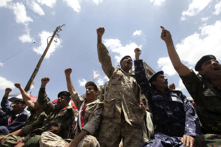 Army and police officers shout slogans during protest to denounce fuel prices hikes and to demand for resignation of government in Sanaa