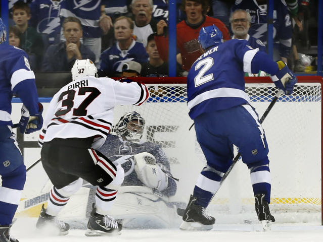 Tampa Bay Lightning goalie Ben Bishop, second from right, cannot stop a shot by Chicago Blackhawks right wing Patrick Kane as Blackhawks' Brandon Pirri (37) and Lightning's Eric Brewer (2) look on during the second period of an NHL hockey game on Thursday, Oct. 24, 2013, in Tampa, Fla. (AP Photo/Reinhold Matay)