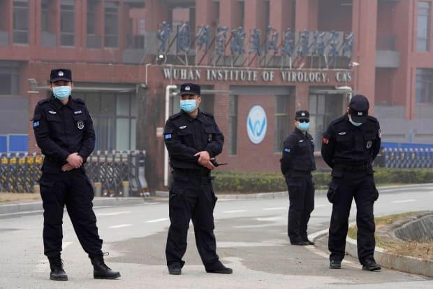 Security personnel gather near the entrance of the Wuhan Institute of Virology during a visit by the World Health Organization team in Wuhan in China's Hubei province on Wednesday, Feb. 3, 2021. (Ng Hah Guan/AP Photo - image credit)