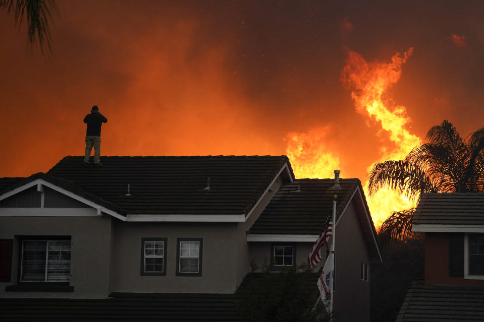 FILE - In this Oct. 27, 2020, file photo, Herman Termeer, 54, stands on the roof of his home as the Blue Ridge Fire burns along the hillside in Chino Hills, Calif. Scientists say the outlook for the western U.S. fire season is grim because it's starting far drier than 2020's record-breaking fire year. (AP Photo/Jae C. Hong, File)