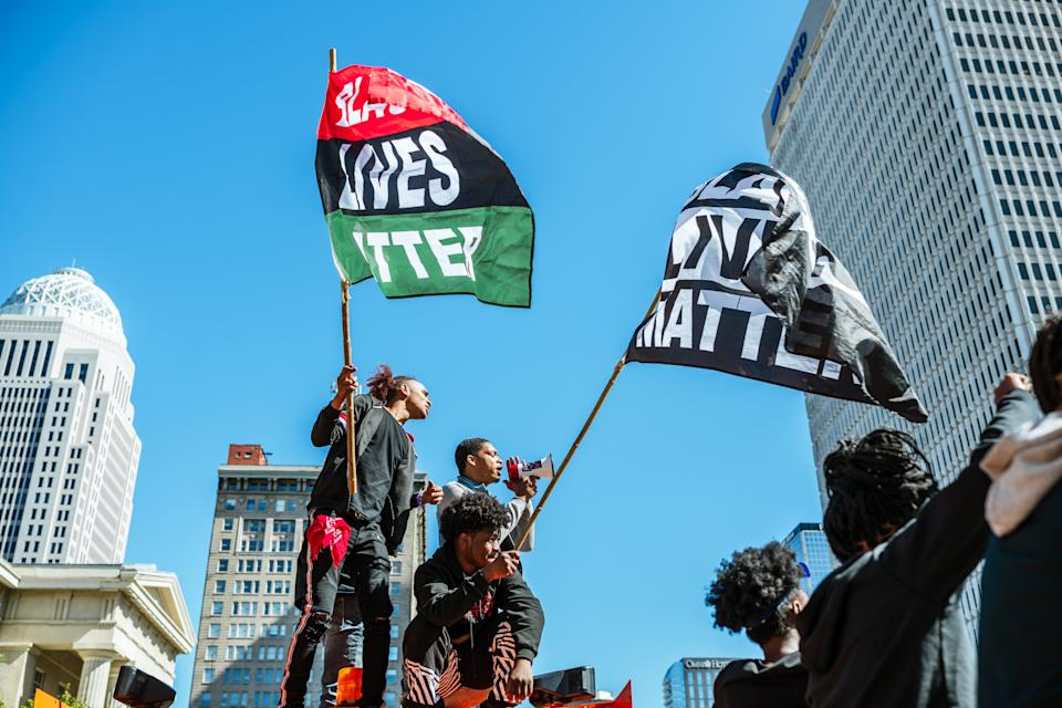 A group of protesters stand on a truck that is being used a road block near Jefferson Square Park on September 30, 2020 in Louisville, Kentucky. (Photo by Jon Cherry/Getty Images)