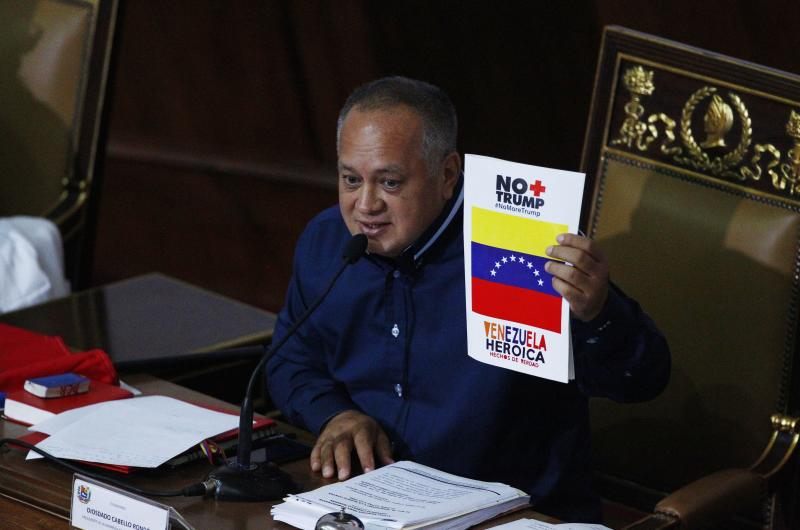 """Venezuela's President of the National Constituent Assembly Diosdado Cabello holds up a sign that in Spanish says """"No more Trump, heroic Venezuela"""" during a session by the legislative body that is stacked with government allies that rivals the opposition-controlled National Assembly in Caracas, Venezuela, Monday, Aug. 12, 2019. Legislators loyal to Venezuelan President Nicolás Maduro on Monday stripped immunity from four opposition lawmakers accused of treason amid a struggle for control of the crisis-stricken nation, bringing to 18 the number of opposition politicians Maduro's government has threatened with criminal prosecution this year. (AP Photo/Leonardo Fernandez)"""