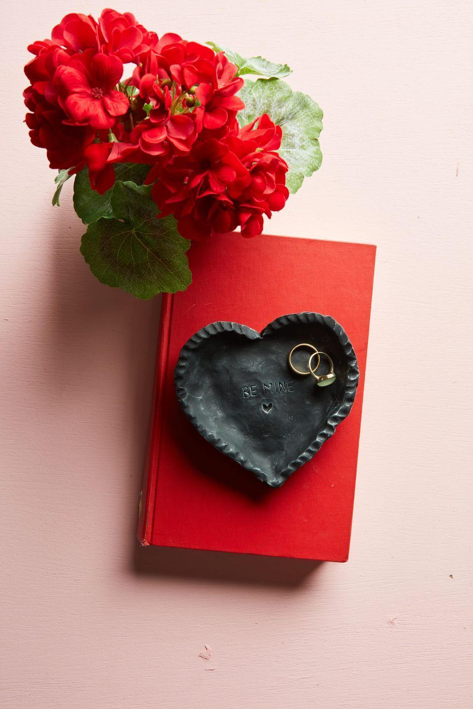 """<p>Ideal for holding rings or other jewelry, this DIY ring plate in simply fashioned from oven-baked clay and will remind that special someone how you feel about them every time they use it.<strong><br></strong></p><p><strong>To make: </strong>Shape modeling clay in a shallow heart-shaped plate. Add a decorative edge and etch a saying in the bottom of the plate with a skewer or sculpting tool. Bake as directed.</p><p><a class=""""link rapid-noclick-resp"""" href=""""https://www.amazon.com/POZEAN-Modeling-Sculpting-Accessories-Beginners/dp/B07XXWXBDP/ref=sr_1_1_sspa?tag=syn-yahoo-20&ascsubtag=%5Bartid%7C10050.g.2971%5Bsrc%7Cyahoo-us"""" rel=""""nofollow noopener"""" target=""""_blank"""" data-ylk=""""slk:SHOP MODELING CLAY"""">SHOP MODELING CLAY</a></p>"""