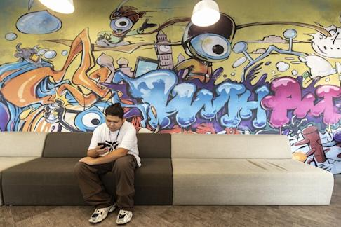 An employee sits in front of a mural at the Ant Group headquarters in Hangzhou, China. Photo: Bloomberg
