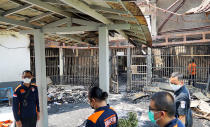 In this photo released by the Indonesian Ministry of Justice and Human Rights, police officers inspect damage cells after a fire at Tangerang Prison in Tangerang, Indonesia, Wednesday, Sept. 8, 2021. A massive fire raged through the overcrowded prison near Indonesia's capital early Wednesday, killing a number of inmates. (Indonesian Ministry of Justice and Human Rights via AP)