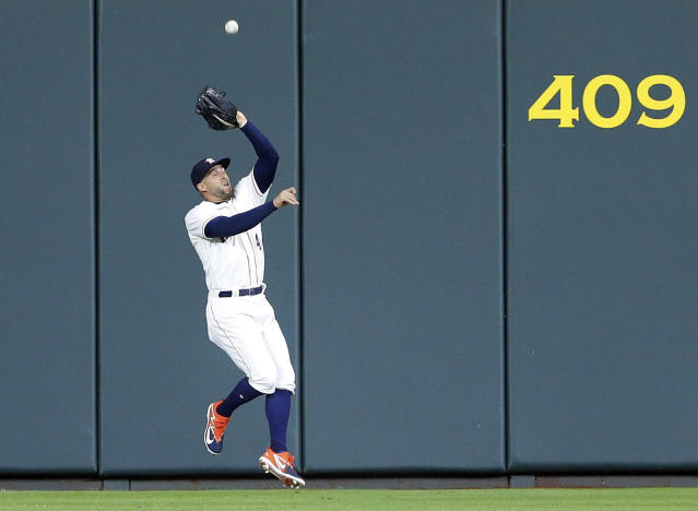 Houston Astros center fielder George Springer (4) makes the catch at the wall on the shot by Cleveland Indians Francisco Lindor during the first inning of a baseball game Sunday, May 20, 2018, in Houston. (AP Photo/Michael Wyke)