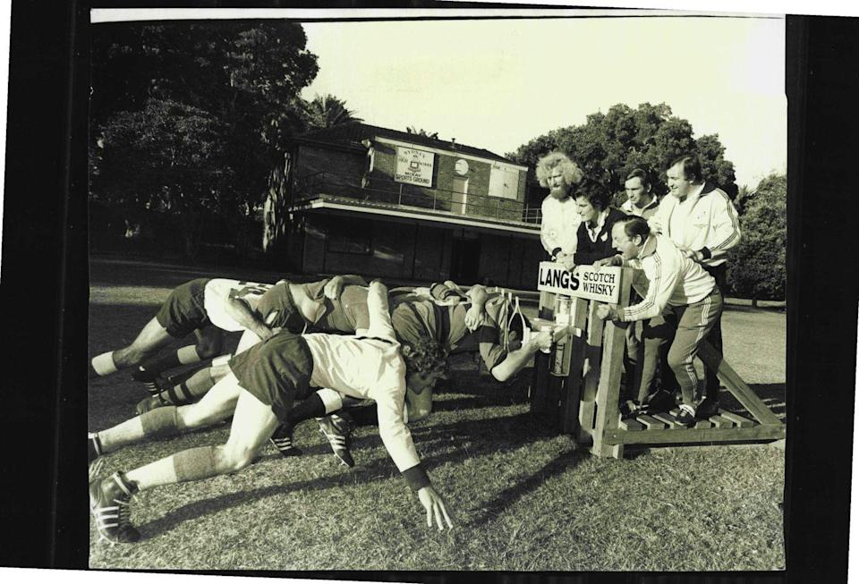 <p>Football players push their coaches on a scrum machine. This method of training is still used today, but the machines aren't made out of wood, like the one seen here in 1975.</p>