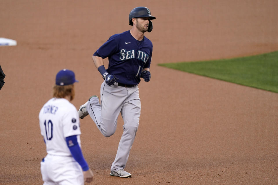 Seattle Mariners' Mitch Haniger, right, heads to third after hitting a solo home run as Los Angeles Dodgers third baseman Justin Turner watches during the first inning of an interleague baseball game Tuesday, May 11, 2021, in Los Angeles. (AP Photo/Mark J. Terrill)