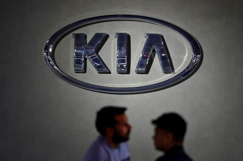Visitors walk past the logo of Kia Motors at its pavilion at the India Auto Expo 2020 in Greater Noida