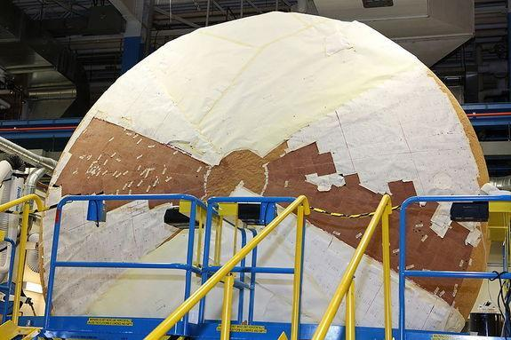 The heat shield for NASA's Orion Multi-Purpose Crew Vehicle, shown here partly wrapped and mounted on its side, is being coated with a layer of thermal protection material at the Textron Defense Systems plant in Wilmington, Mass. It is the worl