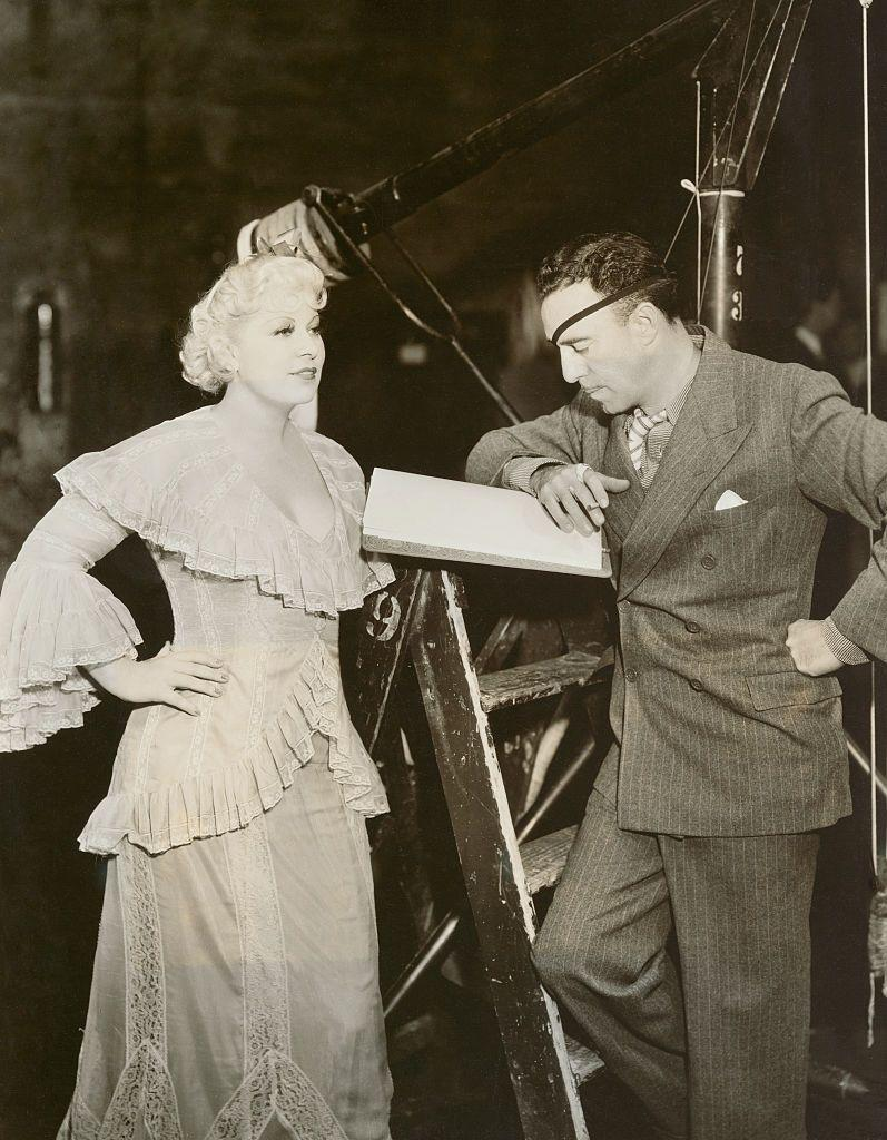 <p>Mae West meets with director Raoul Walsh before shooting a scene for her 1936 film <em>Klondike Annie. </em></p>