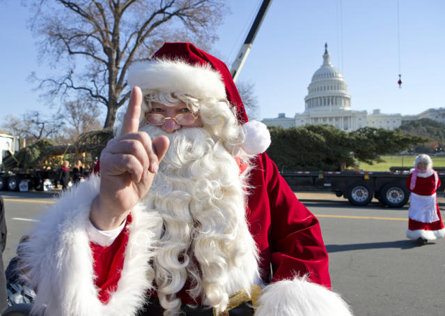 Santa Claus and Mrs. Claus, portrayed by Gerald and Twila Morris of Meeker, Colo., greet visitors on Capitol Hill in Washington, Monday, Nov. 26, 2012, as the 2012 Capitol Christmas Tree, a 73-foot Engelmann Spruce from the White River National Forest, near Meeker, Colo. rear, on truck, arrives. (AP Photo/J. Scott Applewhite)