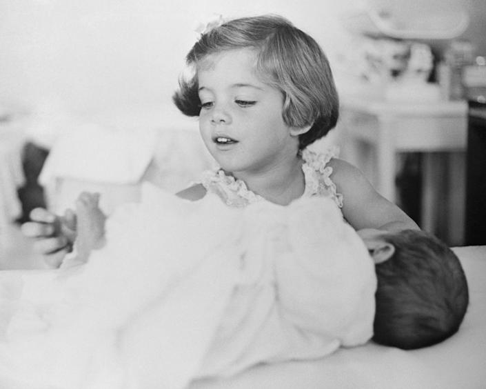 <p>Caroline plays with the toes of her baby brother, John F. Kennedy Jr. </p>