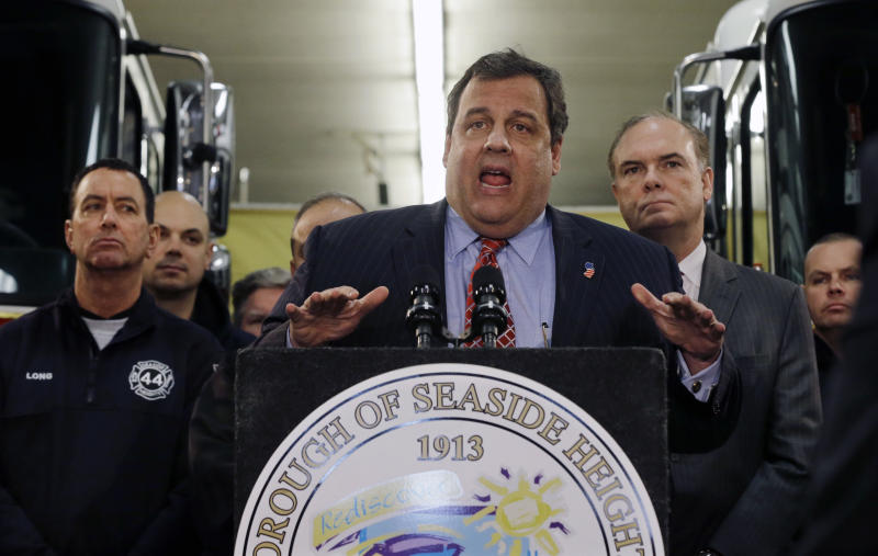 """Bob Martin, center right, Commissioner of the New Jersey Department of Environmental Protection, stands with Seaside Heights firefighters and first responders as they listen to New Jersey Gov. Chris Christie, center, announce his """"Hurricane Sandy Flood Map Regulations"""" Thursday, Jan. 24, 2013, in Seaside Heights, N.J. The town, which was featured in the MTV reality show """"Jersey Shore"""" sustained substantial damage to homes and its boardwalk during Superstorm Sandy. The guidelines will include where and how high to rebuild. (AP Photo/Mel Evans)"""