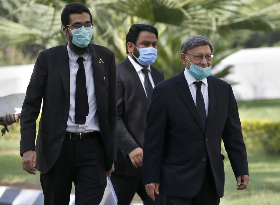 Farooq Naek, center, prosecutor from Sindh provincial government, arrives with his team at the Supreme Court for an appeal hearing of Daniel Pearl case, in Islamabad, Pakistan, Monday, Sept. 28, 2020. Pakistan's Supreme Court is to hear an appeal Monday by the family of slain American journalist Pearl that challenges the acquittal of a British-born Pakistani in the gruesome 2002 beheading of the Wall Street Journal reporter. (AP Photo/Anjum Naveed)