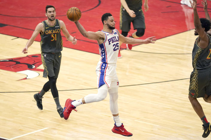 Philadelphia 76ers' Ben Simmons (25) saves the ball from going out of bounds with a long pass as Chicago Bulls' Tomas Satoransky (31) and Thaddeus Young watch during the second half of an NBA basketball game Monday, May 3, 2021, in Chicago. (AP Photo/Charles Rex Arbogast)