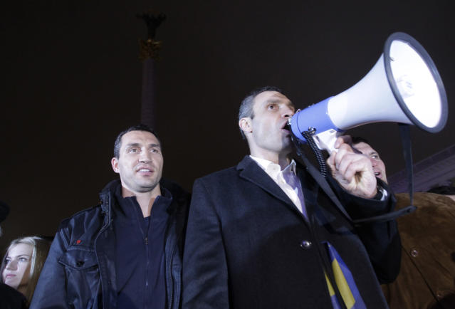 FILE - In this Friday, Nov. 22, 2013 file photo, world heavyweight boxing champion Wladimir Klitschko of Ukraine, left, and lawmaker and chairman of Ukrainian opposition party Udar (Punch), WBC heavyweight boxing champion Vitali Klitschko attend a night rally in support of Ukraine's integration with the European Union in the center of Kyiv, Ukraine. Former heavyweight boxing champion turned philanthropist and management thinker Wladimir Klitschko praises his home country of Ukraine in a year when it has had a starring role in politics and on television in the United States. (AP Photo/Sergei Chuzavkov, file)