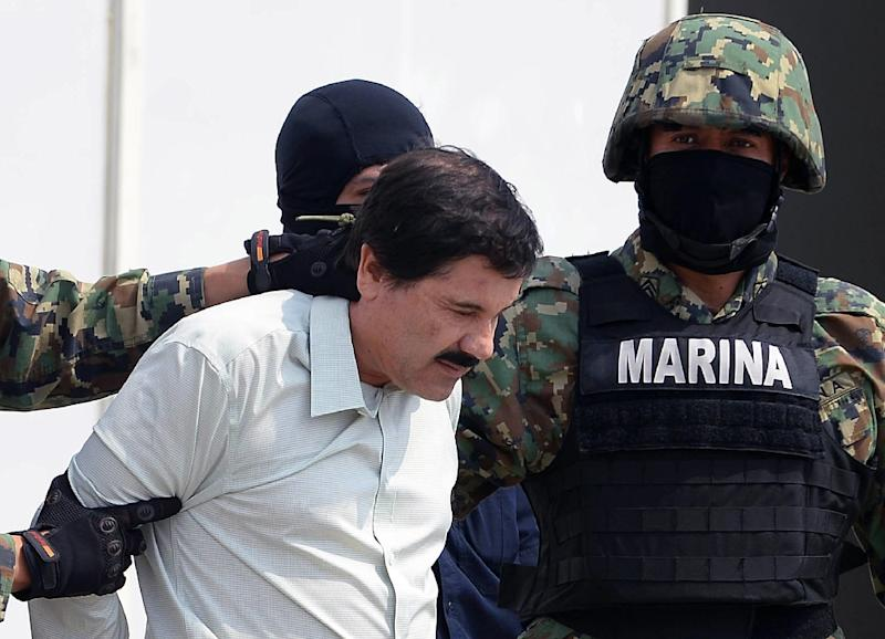 """Mexican drug trafficker Joaquin Guzman Loera, aka """"El Chapo,"""" is escorted by marines as he is presented to the press on February 22, 2014 in Mexico City (AFP Photo/Alfredo Estrella)"""