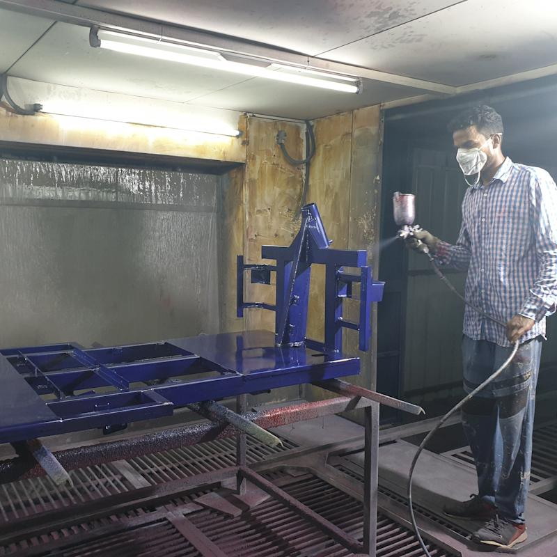 A worker painting the chassis of an e-rickshaw at an electric vehicle manufacturing company in Zirakpur, Punjab. (Photo: Huffpost India)