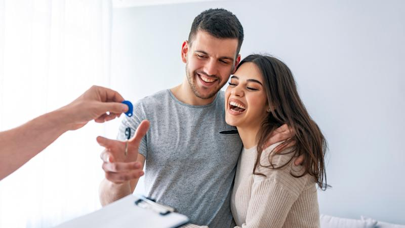Happy couple is taking keys from their new house from hand of estate agent.