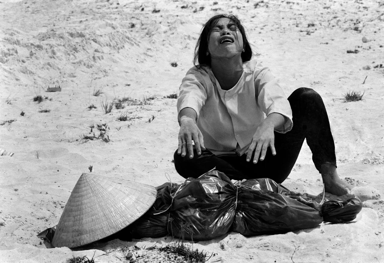 FILE - In this April 1969 file photo shot by Associated Press photographer Horst Faas, a South Vietnamese woman mourns over the body of her husband, found with 47 others in a mass grave near Hue, Vietnam. Faas, a prize-winning combat photographer who carved out new standards for covering war with a camera and became one of the world's legendary photojournalists in nearly half a century with The Associated Press, died Thursday May 10, 2012. He was 79. (AP Photo/Horst Faas, File)