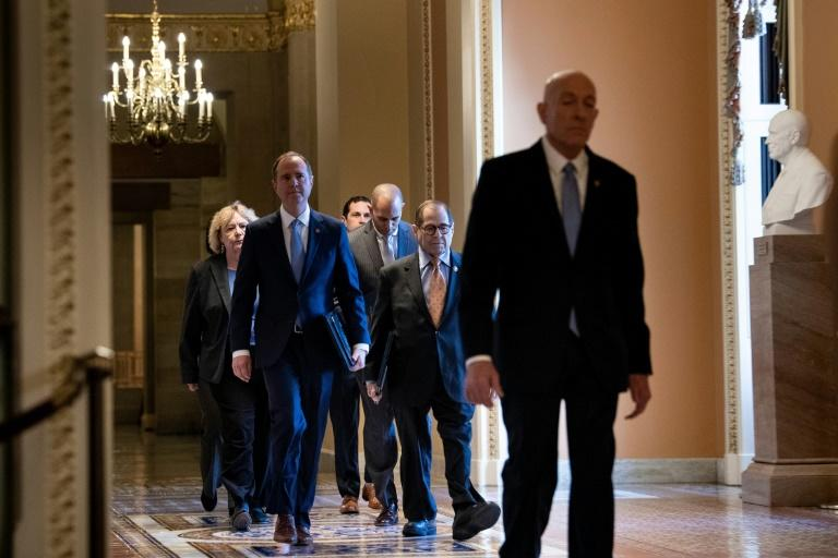The Senate sergeant at arms leads members of the House to the Senate to read out the articles of impeachment against President Donald Trump (AFP Photo/Brendan Smialowski)