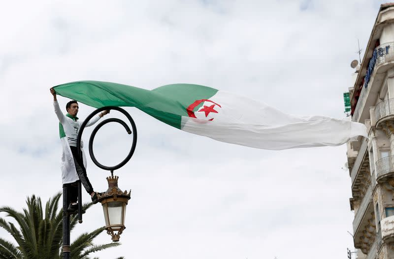 FILE PHOTO: A demonstrator stands on a street pole as he carries a national flag during a protest to push for the removal of the current political structure, in Algiers