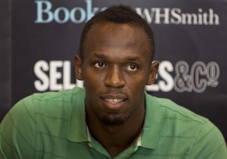 """Jamaican athlete Usain Bolt poses for photographers as he signs copies of his autobiography, """"Faster than Lightning,"""" at Selfridges in central London September 19, 2013. REUTERS/Neil Hall"""