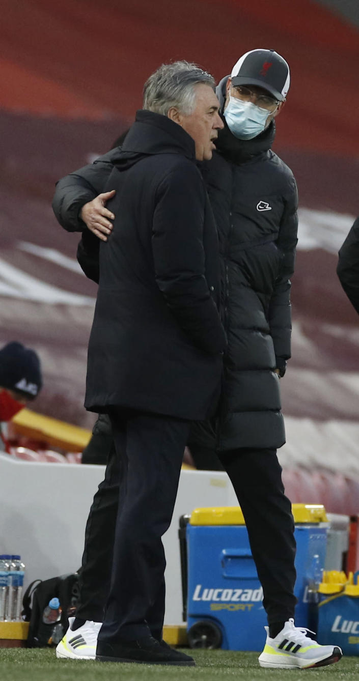Everton's manager Carlo Ancelotti, left, speaks to Liverpool's manager Jurgen Klopp just prior to the start of the English Premier League soccer match between Liverpool and Everton at Anfield in Liverpool, England, Saturday, Feb. 20, 2021. (Paul Ellis / Pool via AP)