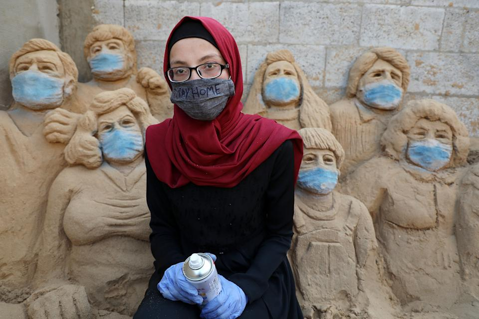 """Sand Artist Rana Ramlawi, 23, works on her sand sculptures depicting the earth with a message reading """"Stay Home"""" at her home in Gaza City during the COVID-19 coronavirus pandemic, in Gaza City, on April 3, 2020.  (Photo by Majdi Fathi/NurPhoto via Getty Images)"""