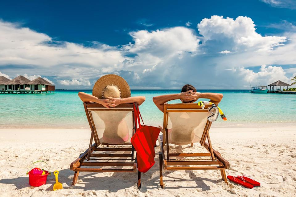 Man and woman sitting on the beach in retirement