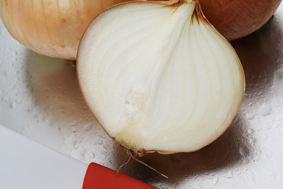 A white onion cut pole-to-pole. Slicing an onion this way makes you cry less compared to orbital sliving.