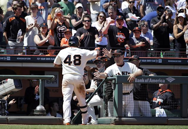San Francisco Giants' Pablo Sandoval (48) is greeted in the dugout by manager Bruce Bochy after Sandoval's solo home run against the Miami Marlins during the fifth inning of a baseball game on Sunday, May 18, 2014, in San Francisco. (AP Photo/Marcio Jose Sanchez)