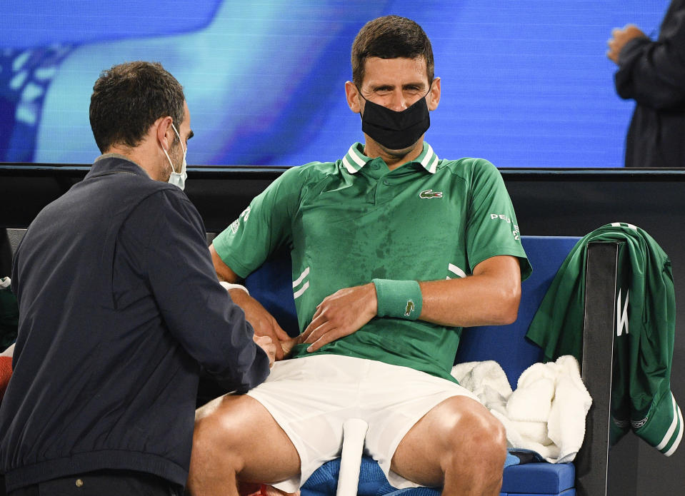 Serbia's Novak Djokovic receives treatment during his third round match against United States' Talyor Fritz at the Australian Open tennis championship in Melbourne, Australia, Friday, Feb. 12, 2021.(AP Photo/Andy Brownbill)