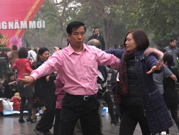 A Vietnamese couple ballroom dance close to a statue in the Vietnamese capital on Sunday, Feb. 16, 2014. Anti-China protestors hoping to lay wreathes at the statue said they believed the dancers were deployed by the government to stop them gathering there. The Vietnamese government is highly wary of public protests, and normally seeks to quash them. (AP Photos/Chris Brummitt)