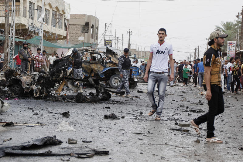 Iraqi security forces and civilians inspect the scene of a car bomb attack in the Kamaliyah neighborhood, a predominantly Shiite area of eastern Baghdad, Iraq, Monday, May 20, 2013. A wave of car bombings across Baghdad's Shiite neighborhoods and in the southern city of Basra killed and wounded scores of people, police said. (AP Photo/ Hadi Mizban)