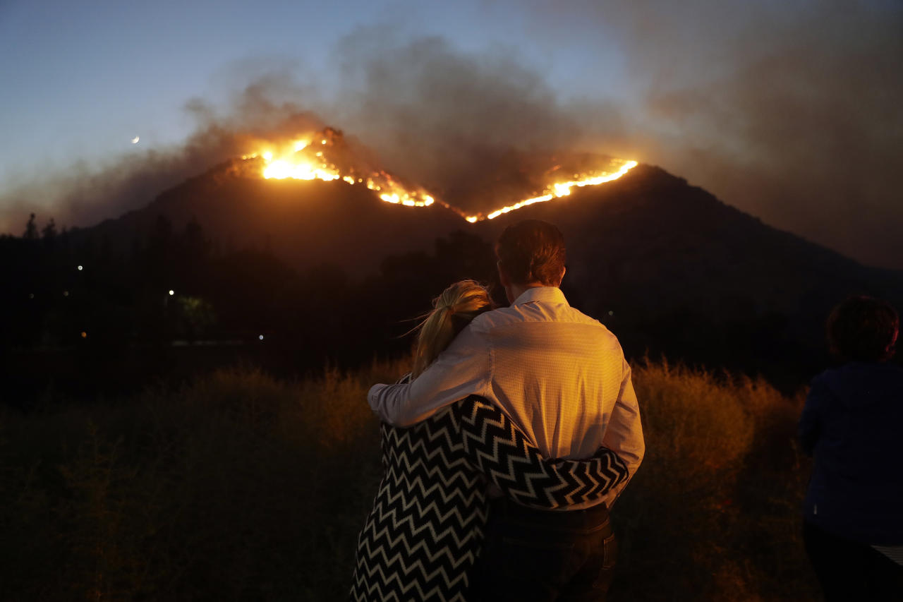 <p>Roger Bloxberg, right, and his wife Anne hug as they watch a wildfire on a hill top near their home Friday. Image: AP </p>