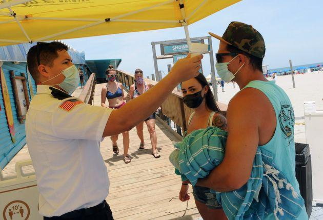 People wear face masks and undergo mandatory temperature checks before entering the pier on Independence Day in Cocoa Beach, Florida