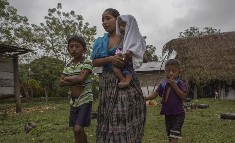 Claudia Maquin, 27, walks with her three children, Abdel Johnatan Domingo Caal Maquin, 9, left, Angela Surely Mariela Caal Maquin, 6 months, middle, and Elvis Radamel Aquiles Caal Maquin, 5, right, as they leave Domingo Caal Chub's house, Claudia's father in law, in Raxruha, Guatemala, Saturday, Dec. 15, 2018. Claudia Maquin's daughter, 7-year-old Jakelin Amei Rosmery Caal, died in a Texas hospital, two days after being taken into custody by border patrol agents in a remote stretch of New Mexico desert. (AP Photo/Oliver de Ros)