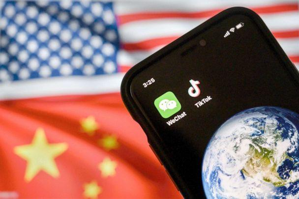 PHOTO: A mobile phone displays the logos for Chinese apps WeChat and TikTok in front of a monitor showing the flags of the United States and China on an internet page in Beijing, Sept. 22, 2020. (Kevin Frayer/Getty Images, FILE)