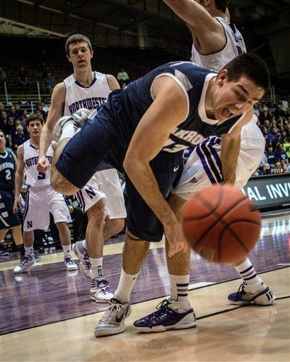Akron's Nikola Cvetinovic loses control of ball as he tries to get past Northwestern's Davide Curletti during the first half in a first-round college basketball game in the NIT in Evanston, Ill., on Tuesday, March 13, 2012. (AP Photo/Charles Cherney)