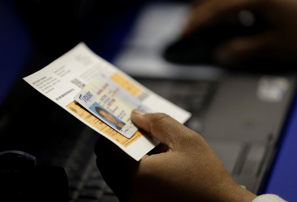 Close-up of hand holding a Texas driver's license and voting envelope