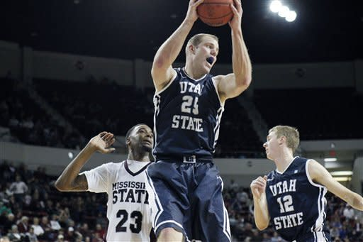 Utah State center Jordan Stone (25) yells as he pulls down a rebound past Mississippi State forward Arnett Moultrie (23) and Utah State forward Danny Berger (12) in the first half of their NCAA college basketball game in Starkville, Miss., Saturday, Dec. 31, 2011. (AP Photo/Rogelio V. Solis)