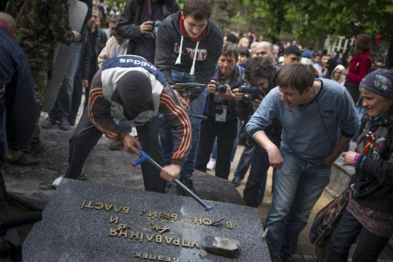 """Pro-Russian protesters break up the words """"Ukrainian the Security Service"""" next to the Ukrainian regional office of the Security Service in Donetsk, eastern Ukraine, Saturday, May 3, 2014, which has been captured to honor the memory of fallen comrades during fighting with pro-Ukrainian activists in Odessa on Friday. In Donetsk, the largest city in the insurgent east, demonstrators who stormed the local office of the Ukrainian Security Service on Saturday evening shouted """"We will not forgive Odessa."""" No police were deployed to block the building takeover. (AP Photo/Alexander Zemlianichenko)"""