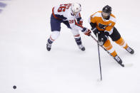 Washington Capitals center Nic Dowd (26) and Philadelphia Flyers center Sean Couturier (14) vie for the puck during the second period of an NHL hockey playoff game Thursday, Aug. 6, 2020, in Toronto. (Cole Burston/The Canadian Press via AP)