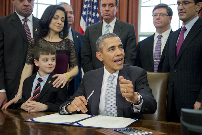 President Barack Obama with Jake Miller, left, and Ellyn Miller, behind Jake, brother and mother of Gabriela Miller, talks about the Gabriella Miller Kids First Research Act, before signing it into law, Thursday, April 3, 2014, in the Oval Office of the White House in Washington. (AP Photo/Manuel Balce Ceneta)