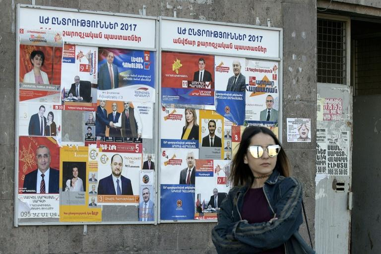 A woman walks past election posters in the Armenian capital of Yerevan, ahead of landmark parliamentary elections in the landlocked nation of 2.9 million